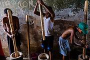 Men pounding millet at Roça Agostinho Neto, in São Tomé island.
