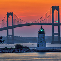 Newport Harbor Light also known as Goat Island Lighthouse in Newport , Rhode Island. This historic Rhode Island lighthouse with its iconic white stone tower and a fixed green light is located in Narragansett Bay guiding the way into Newport Harbor. In the background towers the famous Newport Bridge.<br /> <br /> Newport Harbor Light photography photos are available as museum quality photo, canvas, acrylic, wood or metal prints. Wall art prints may be framed and matted to the individual liking and New England interior design projects decoration needs.<br /> <br /> Good light and happy photo making!<br /> <br /> My best,<br /> <br /> Juergen