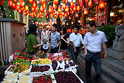 """A fruit seller plies her trade as red lanterns hang overhead along Guijie food street, the famous eating street in Beijing, China. known to locals as 'Ghost Street' as it remains open 24 hours a day, eating on Ghost Street is about more than food and drink, it's a way of life for many Beijingers. Tucked behind Dongzhimen Street, """"Ghost Street"""" stretches 1.5km and contains more than 150 shops, including 100 restaurants, making it one of the most unique streets in Beijing."""