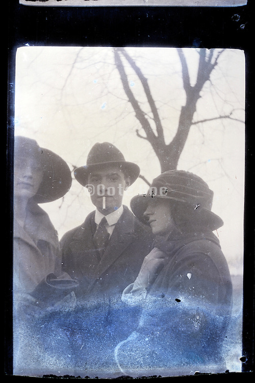 fading image of young adult man and two women early 1900s