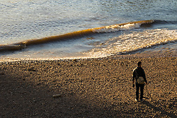 Battersea, London, April 29th 2015. After a day that started off with gloomy, damp weather, Londoners are rewarded with a beautiful spring sunset. PICTURED: A man strolls along the shore, enjoying the evening sun at low tide.