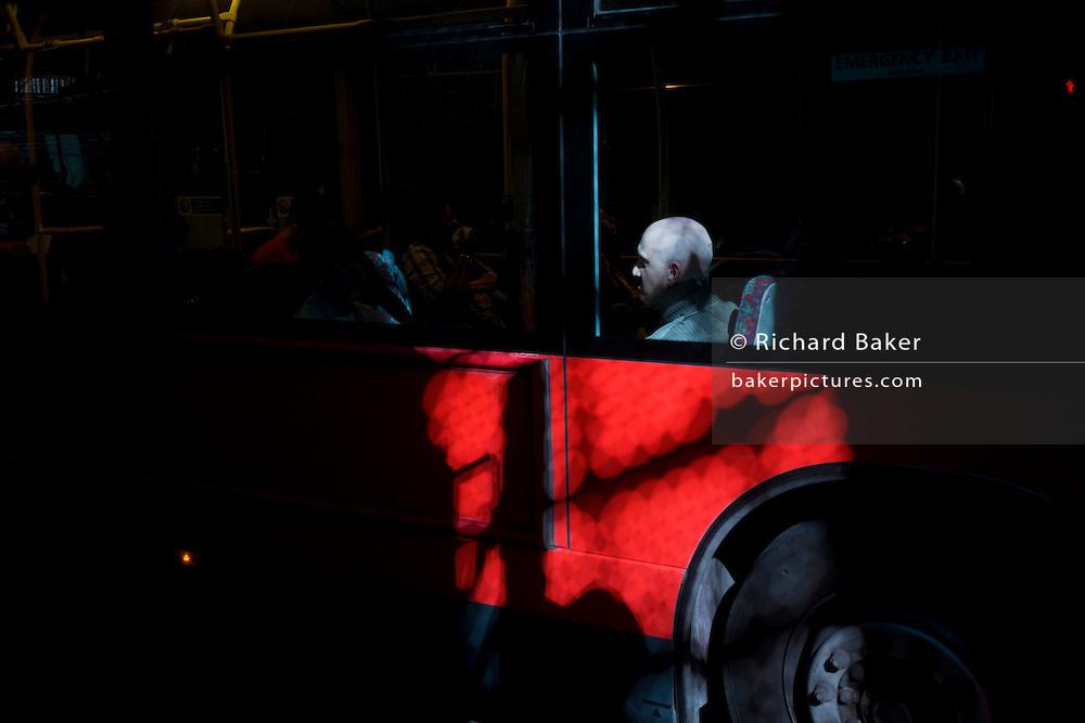 Bald-headed London bus passenger sits near window as sunlight passes through a tunnel roof.