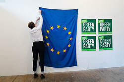 © Licensed to London News Pictures. 08/05/2019. London, UK.  A member of the Green Party puts up a European Union flag  at the Green Party European election campaign launch, held at the Candid Arts Trust.  Photo credit: Vickie Flores/LNP