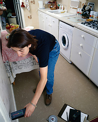 London Borough of Haringey Housing Officer checking kitchen wall for damp in council flat UK