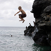 A young boy jumps from a large crop of rock into the water at Waimea Bay on the North Shore of Oahu in Hawaii.