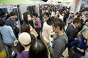 commuter with an mp3 player waiting with others to enter the train Tokyo Japan