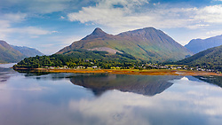 Aerial view from drone of Sgorr na Ciche or the Pap of Glencoe and village of Invercoe (left) and Glencoe village beside Loch Leven in Glen Coe , Lochaber, Scottish Highlands, Scotland, UK