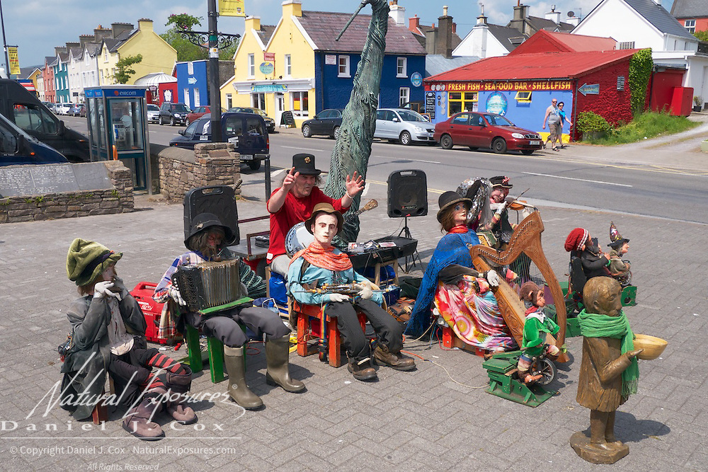 A street musician with an unusual cast of characters on main street of Dingle, Ireland