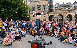 Edinburgh, Scotland, UK. 8th August  2021. On a sunny Sunday afternoon the Royal Mile was busy with visitors looking for the limited street entertainment provided during the much scaled back Edinburgh Fringe Festival this year. Two stages are provided for performers and these proved popular throughout the day. Pic; Crowd watches escape artist on the Royal Mile. Iain Masterton/Alamy Live news.