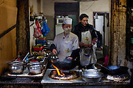 Cooking in an alleyway restaurant in Chengdu