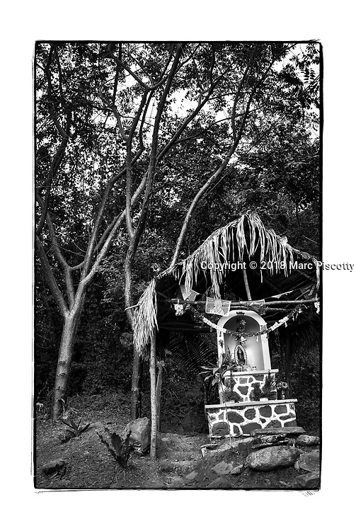 SHOT 2/9/18 5:40:16 PM - A small roadside capilla under a palapa near Chacala, Mexico. Capillas are common along the roads and highways of Mexico which is heavily Catholic and are often dedicated to certain patron saints or to the memory of a loved one that has passed away. Often times they contain prayer candles, pictures, personal artifacts or notes. (Photo by Marc Piscotty / © 2018)