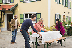 Family preparing a picnic table outside at farmhouse, Bavaria, Germany
