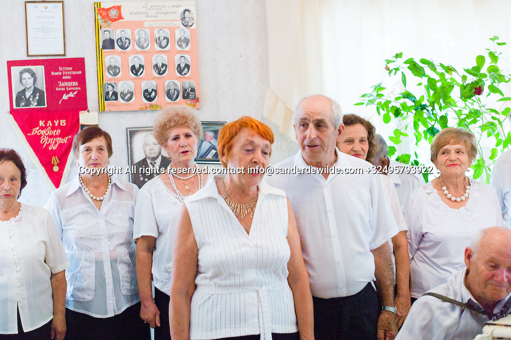 20150829  Moldova, Transnistria,Pridnestrovian Moldavian Republic (PMR) Dubushari. Veterans sing old soviet songs in the soviet clubhouse in Dubushari.The walls are decorated with old pictures and soviet signs, all singers are dressed in white.