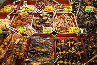 """Nishiki Market Take-Away Foods; Nishiki Market is a narrow shopping street made up of more than one hundred vendors.  Various kinds of fresh foods including many Kyoto specialties such as pickles and Japanese sweets, as well as fresh seafood and vegetables are sold.  Known as """"Kyoto's Kitchen"""" Nishiki Market's history goes back several centuries and many stores have been operated by the same families for generations."""