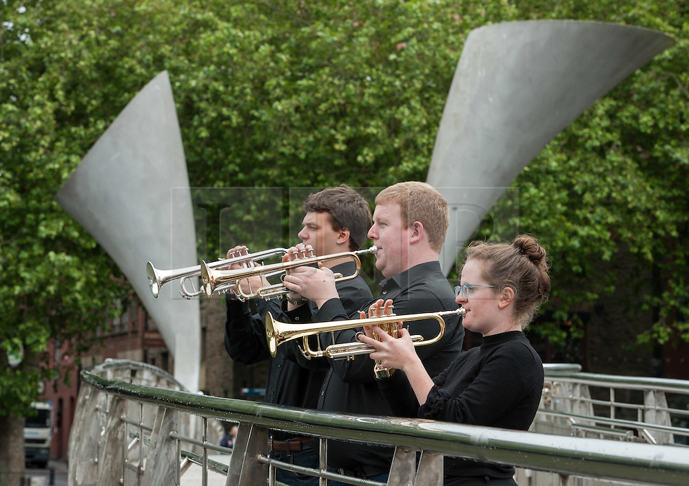 """© Licensed to London News Pictures. 27/07/2015. Bristol, UK.  """"Fanfare for Bristol"""", titled """"At the Top of the Tide"""", composed by David Mitcham, commissioned by Bristol Proms 2015.  Picture shows trumpeters l-r: Gideon Brooks, Chris Hart, Helen Whitemore, playing on Pero's Bridge in Bristol Harbourside.  The fanfare was performed live for the Mayor of Bristol, George Ferguson and Artistic Director of the Bristol Old Vic, Tom Morris for the first time at Bristol's famous Temple Mead train station, heralding the opening of the Bristol Proms 2015.  David Mitcham's  """"At the Top of the Tide"""" was inspired by 'Bristol's inextricable links to the sea'.  The first performance by Arc Brass took place outside the Engine Shed, and throughout the day, performances took place at the Watershed, Pero's Bridge, the Wills Memorial Bell Tower and finally at Bristol Old Vic itself. David Mitcham, who has worked extensively for the BBC Natural History Unit based in Bristol said: """"I am thrilled that my Fanfare """"At the Top of the Tide"""" has been chosen for the city of Bristol and to open Bristol Proms 2015. I hope the Fanfare represents the rich diversity of Bristol, its maritime and industrial heritage as well as being a celebration of the spirit of the city and the energy it will carry into the future.""""  Bristol Proms 2015 runs from today, 27th July to 1st August and features some of the world's finest musicians including Alison Balsom, Miloš Karadaglić, Pumeza Matshikiza and Daniel Hope.  Photo credit : Simon Chapman/LNP"""