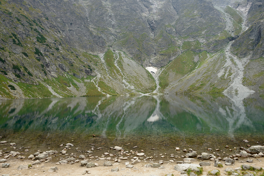 The landscape of the Tatra Mountains is reflected in Czarny Staw pod Rysami (which means Black Lake below Mount Rysy), which sits at an elevation of 1,583 meters within the Tatra National Park in Poland. This small lake is located above the more famous Morskie Oko.