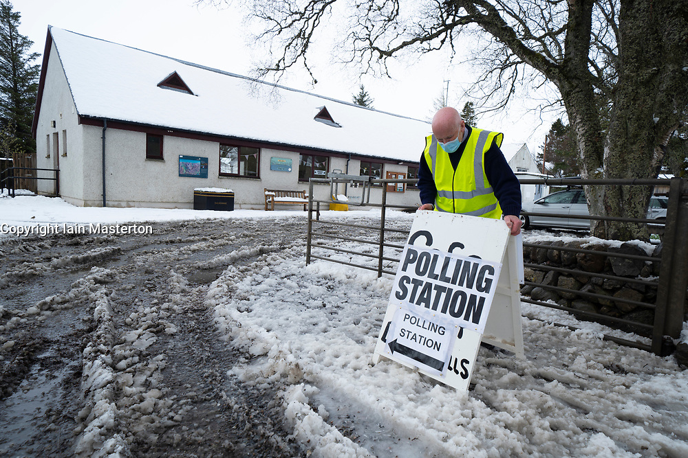 Dalwhinnie, Scotland, UK. 6 May 2021. Overnight snow in at the polling station in the village hall in Dalwhinnie in the Scottish Highlands. The public go to the polls today in Scotland to elect new Members of the Scottish Parliament. Pic; Information Officer for the polling station, Bill Carr, working at Dalwhinnie Village Hall today.  Iain Masterton/Alamy Live News