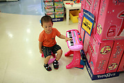 A young toddler plays at a toy store in Shanghai, China on 13 August, 2011.  The director of the Population and Family Planning Commission of Guangdong, China's most populous province, has openly criticized the country's one-child policy, and said he has submitted policy change for approval to relaxation of the rules.