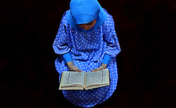 June 14, 2017 - Khan Younis, Gaza Strip - A Palestinian girl reads a copy of the Koran, Islam's holiest book, on the Muslim holy fasting month of Ramadan, at Hamad Mosque in Khan Younis in the southern Gaza Strip, June 14, 2017. Ramadan is sacred to Muslims because it is during that month that tradition says the Koran was revealed to the Prophet Mohammed. The fast is one of the five main religious obligations under Islam. More than 1.5 billion Muslims around the world will mark the month, during which believers abstain from eating, drinking, smoking and having sex from dawn until sunset  (Credit Image: © Ashraf Amra/APA Images via ZUMA Wire)