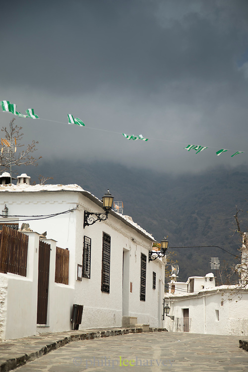 View of street and storm clouds, Bubion, Andalusia, Spain