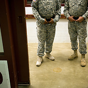 Camp 5 guards standing in the entrance to the spoke at the Guantanamo Bay Detention Facility in Guantanamo Bay, Cuba. The detainees held in this facility were captured after the attacks on the United States on September 11, 2001. In 2009 US president Barack Obama ordered the closure of the facility, yet to date it still remains open. These Photos were reviewed by military officials before release.