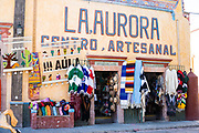 Shops selling arts and craft items in the town square in the beautiful colonial village of Bernal, Queretaro, Mexico. Bernal is a quaint colonial town known for the Pena de Bernal, a giant monolith which dominates the tiny village is the third highest on the planet.
