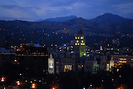 The lights of Salt Lake City at dusk, below blue mountains and skies.