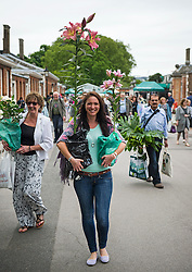 © London News Pictures. 23/05/2015. London, UK. Natalie Miller holding the plants she bought. Members of the public carry exhibitors' plants from the 2015 Chelsea Flower show, which ends today (Sat). The Royal Horticultural Society flagship flower show has been held at the Royal Hospital in Chelsea since 1913. Photo credit: Ben Cawthra/LNP