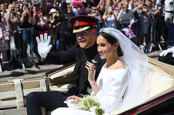 Prince Harry and Meghan Markle ride in an Ascot Landau past Victoria Barracks in Windsor after their wedding in St George's Chapel.