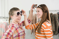 Young women trying sunglasses at fashion store