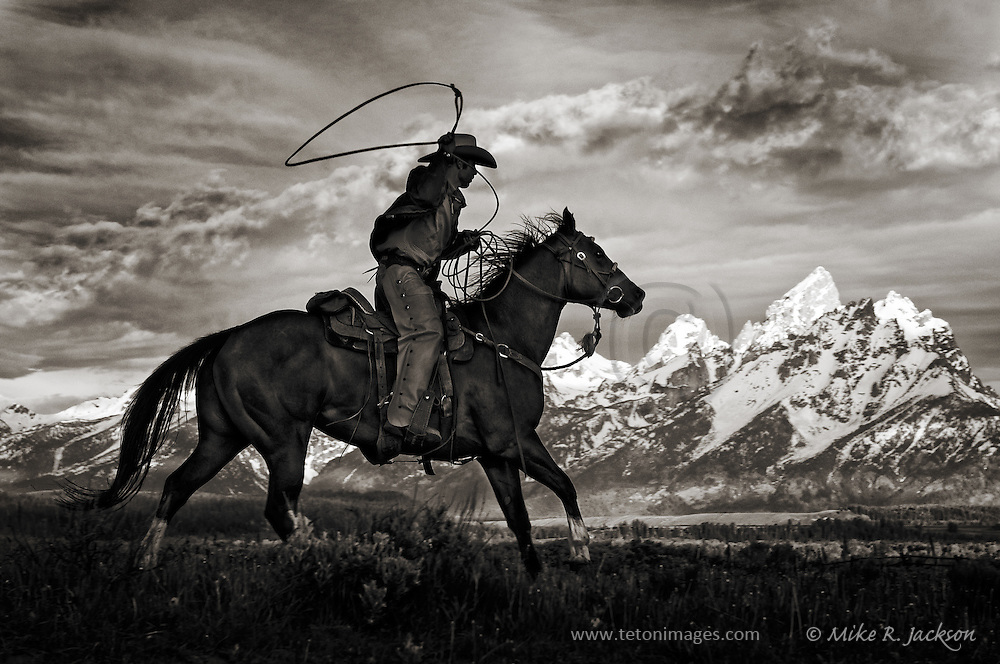 A silhouetted wrangler and horse in front of the Grand Teton mountain range.