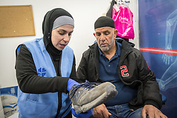 26 February 2020, Abu Dis, Palestine: Nurse Najwa Hawamdeh administers a foot exam of patient 49-year-old Diabetes patient Issam Muhsan from Abu Dis. Here, checking the size of his foot vis-a-vis his shoe, to test that his shoes are spacious enough, as Diabetes patients often develop sensitive feet. The testing is an annual routine for Diabetes patients. In an effort to make Diabetes services more accessible to people in the West Bank, the Augusta Victoria Hospital offers a Mobile Diabetes Clinic, which moves around to various locations in the West Bank, offering screening and routine testing for Diabietes and the symptoms it causes.