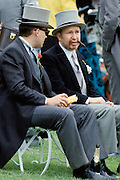 Racegoers sitting on bench in front of the Grandstand at Epsom Racecourse for Derby Day, UK