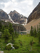 A woman enjoys the view of Lefroy Lake on the Lake Oesa Trail with  Glacier Peak in the background, in Yoho National Park, near Field, British Columbia, Canada; MR available