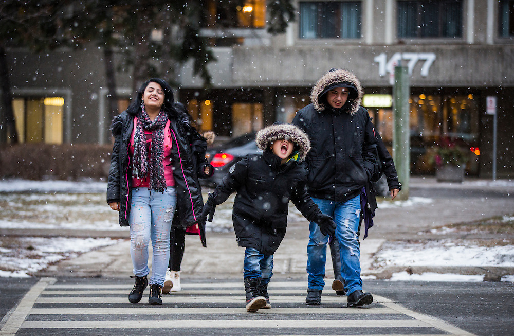 Syrian refugee Nasimi Batal Al Hasan, walks with his brother Ali (right), and his sister Fusie (left), outside during snowfall outside of their apartment building in Mississauga, Ontario, Canada, Thursday January 21, 2016.   (Mark Blinch for the BBC)