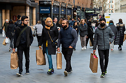 © Licensed to London News Pictures. 12/04/2021. LONDON, UK.  People carrying their shopping in Leicester Square following the UK government's coronavirus roadmap out of lockdown which allowed non-essential shops to reopen today.  Photo credit: Stephen Chung/LNP