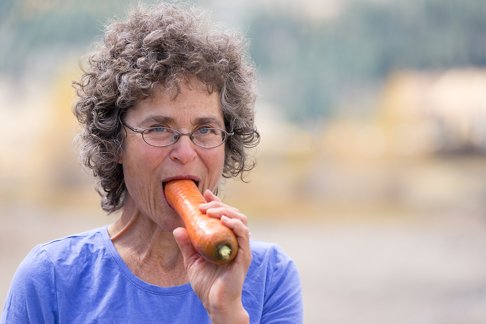 Woman eating a large carrot.