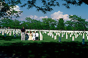 Family at grave in Fort Snelling cemetery on Memorial Day age 40 and teenagers.  St Paul Minnesota USA