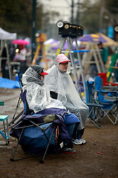 04 March 2014. New Orleans, Louisiana.<br /> Fat Tuesday. Mardi Gras Day.  Revelers wrap up against the cold and wet along St Charles Avenue ahead of the parades.<br /> Photo; Charlie Varley/varleypix.com