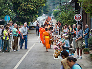 "12 MARCH 2016 - LUANG PRABANG, LAOS: Some tourists watch other tourists give alms to Buddhist monks during the morning tak bat in Luang Prabang. Luang Prabang was named a UNESCO World Heritage Site in 1995. The move saved the city's colonial architecture but the explosion of mass tourism has taken a toll on the city's soul. According to one recent study, a small plot of land that sold for $8,000 three years ago now goes for $120,000. Many longtime residents are selling their homes and moving to small developments around the city. The old homes are then converted to guesthouses, restaurants and spas. The city is famous for the morning ""tak bat,"" or monks' morning alms rounds. Every morning hundreds of Buddhist monks come out before dawn and walk in a silent procession through the city accepting alms from residents. Now, most of the people presenting alms to the monks are tourists, since so many Lao people have moved outside of the city center. About 50,000 people are thought to live in the Luang Prabang area, the city received more than 530,000 tourists in 2014.       PHOTO BY JACK KURTZ"