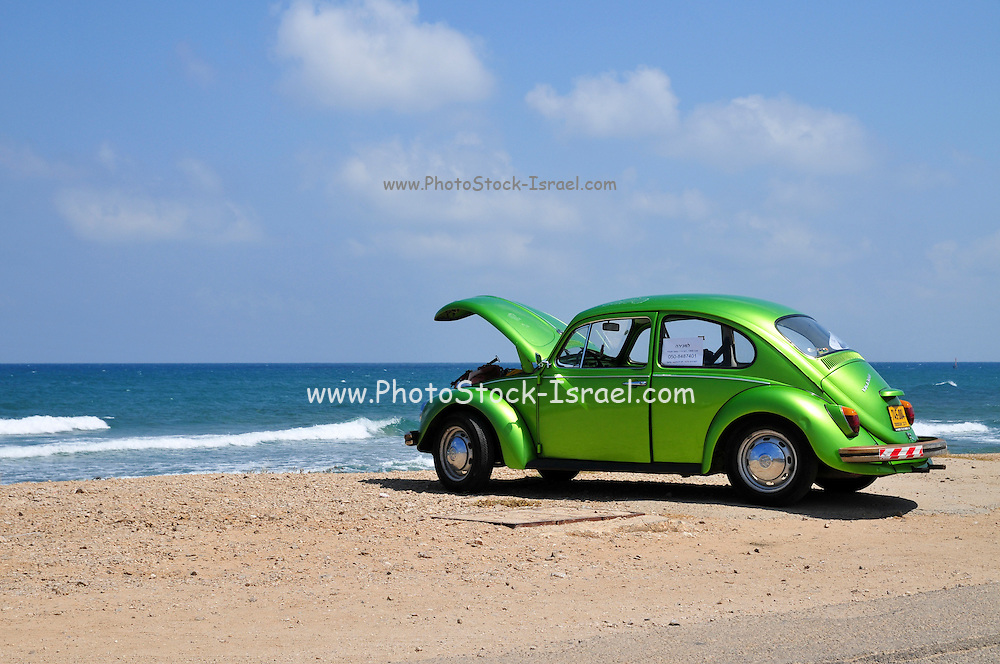 A green 1969 Volkswagen Beetle on the beach