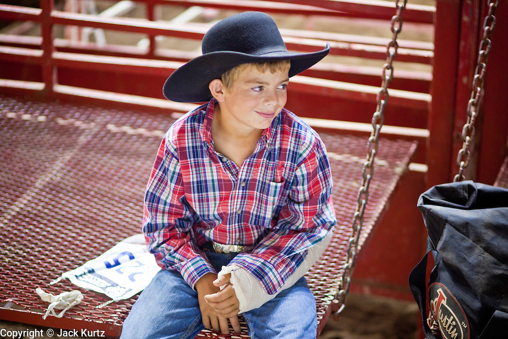 """01 SEPTEMBER 2011 - ST. PAUL, MN:  A high school student with a broken arm behind the chutes of the high school rodeo at the Minnesota State Fair. The Minnesota State Fair is one of the largest state fairs in the United States. It's called """"the Great Minnesota Get Together"""" and includes numerous agricultural exhibits, a vast midway with rides and games, horse shows and rodeos. Nearly two million people a year visit the fair, which is located in St. Paul.  PHOTO BY JACK KURTZ"""