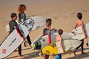 Israel, Mediterranean sea, Group of young surfers on the beach