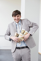 Portrait of businessman holding coffee cups to go for all
