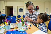 A PACT support worker does some art work with one of the children during a family visit in HMP Brixton, South London on the 26th of July 2016, London United Kingdom. The Prisoner Advice & Care Trust (PACT) organise special family days that help the men inside the prison connect with and support their partners and children on the outside. (photo by Andy Aitchison)