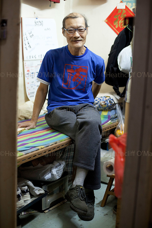Mcc0034706 .  Daily Telegraph...Unemployed Mr Lam in his tiny 25 sq ft single room apartment in Kowloon, Hong Kong where he lives on benefits..Increasingly poorer people are having to live in partitioned single room apartments at extortionate rents as property prices on the crowded former colony rise beyond their reach...Hong Kong 5 October 2011