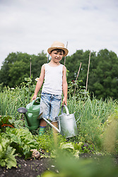 Little boy with watering cans in a community garden, Bavaria, Germany