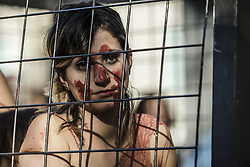 December 11, 2016 - A naked animal rights activist covered with fake blood crouches in a cage during one of the most impacting animal rights protests staged in Barcelona to denounce the use of animal skins and fur (Credit Image: © Matthias Oesterle via ZUMA Wire)
