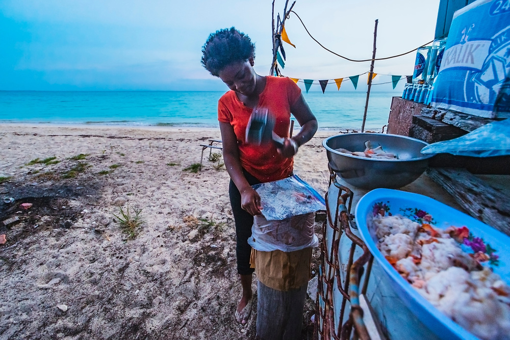 A young woman, working at her mother's restaurant, uses a mallet to pound conch meat in a plastic bag on Cat Island, Bahamas.