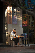 Senior man sitting at small table outside cafe, Casablanca, Morocco